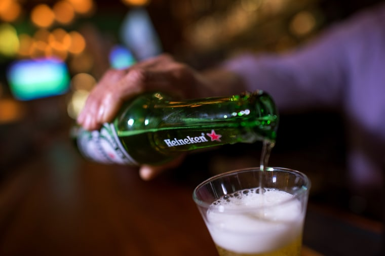 Image: A man pours Heineken beer in a glass