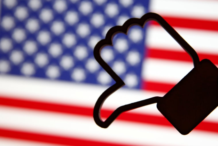 Image: A 3D-printed Facebook Like symbol is displayed inverted in front of a U.S. flag in this illustration
