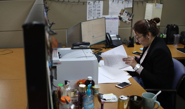 Image: Lorena Jofre works at her desk at Wilson, Washburn and Forster Insurance company