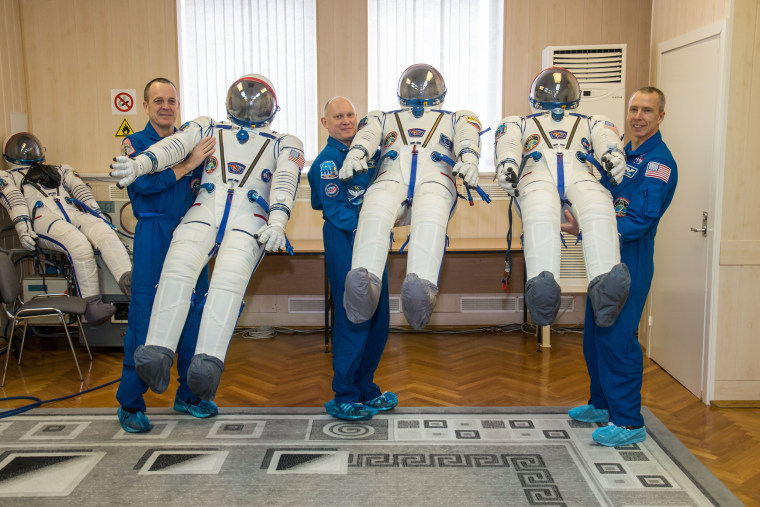 Image: jsc2018e010883 - At the Baikonur Cosmodrome in Kazakhstan, Expedition 55 crewmembers Ricky Arnold of NASA (left), Oleg Artemyev of Roscosmos (center) and Drew Feustel of NASA (right) pose for pictures with their Russian Sokol launch and entry suits