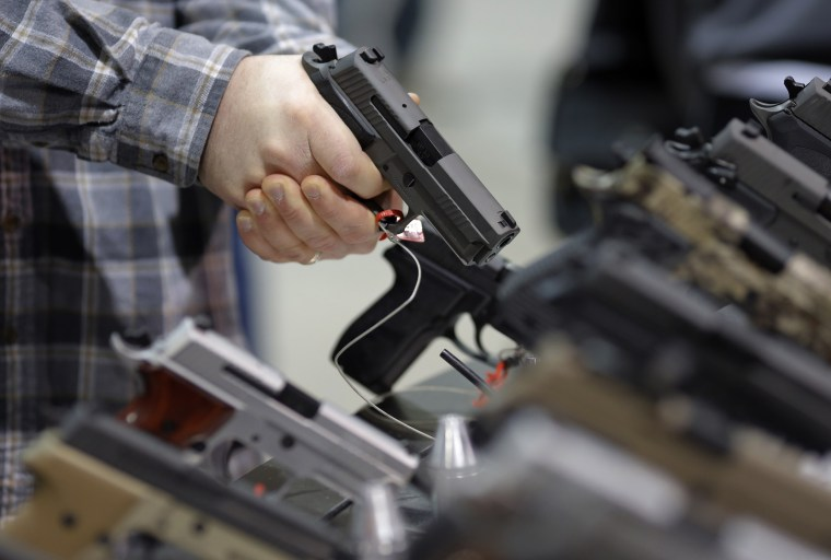 Image: A visitor holds a pistol at a gun display during a National Rifle Association outdoor sports trade show