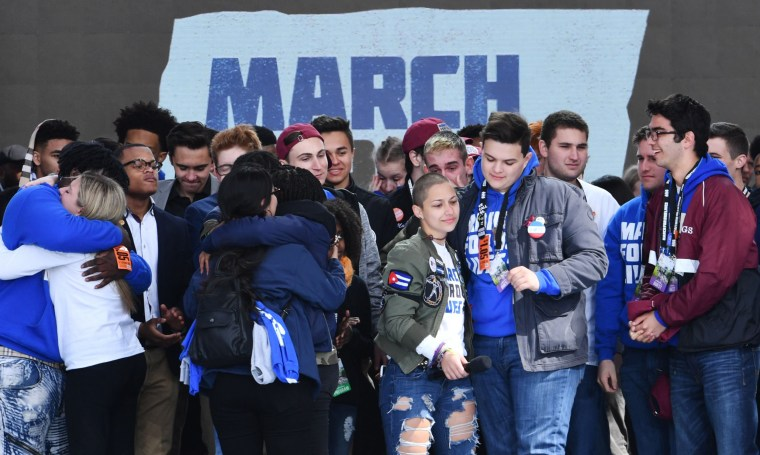 Image: Marjory Stoneman Douglas High School student Emma Gonzalez, center right,  gathers with other students