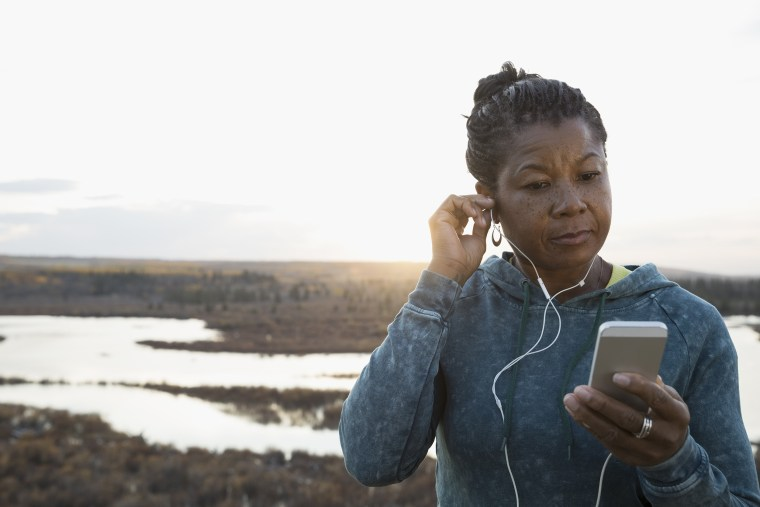 Image: Woman runner listening to music with mp3 player and earbuds overlooking lake