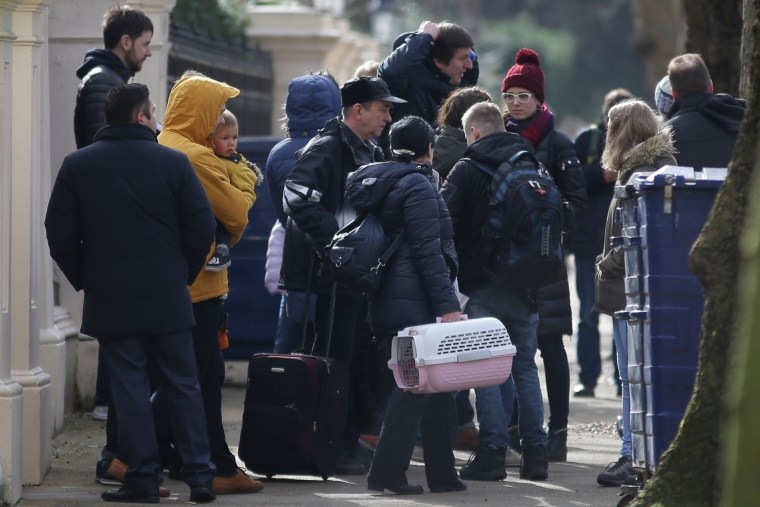 Image: People carrying luggage leave the Russian Embassy in London