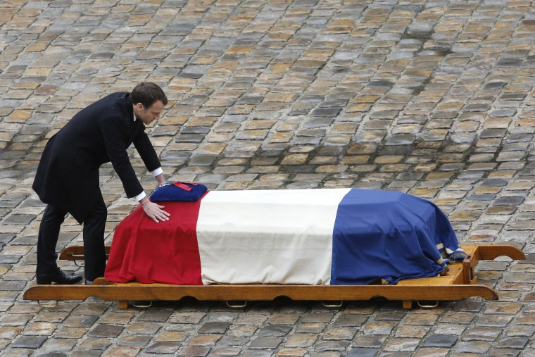 Image: French President Emmanuel Macron leans at the coffin of Lt. Col. Arnaud Beltrame