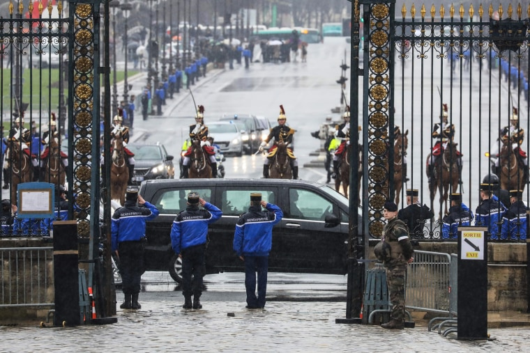 Image: Gendarmes stand at attention as the convoy of French Republican Guards escorting the coffin