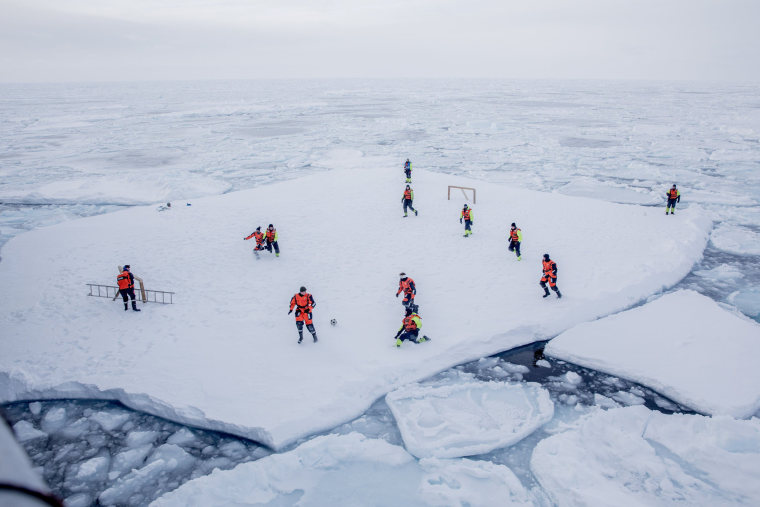 Image: KV Svalbard's crew play soccer as they are protected from polar bears by armed guards in the arctic environment in the sea around Greenland