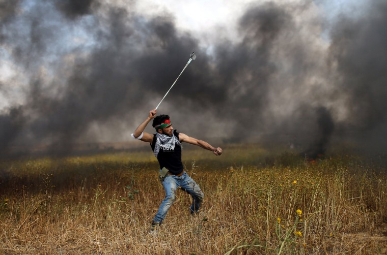 Image: A protester hurls stones at Israeli troops during clashes along the Israeli border with Gaza
