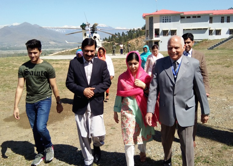 Image: Malala Yousafzai walks with her father, Ziauddin (2L), brother Atal (L) and Guli Bagh, the principal of the all-boys Swat Cadet College.