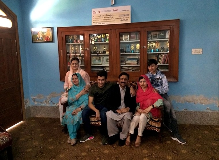Image: Malala Yousafzai, second right, poses in her old home with family and with Pakistan's Information Minister Marriyum Aurangzeb in the center.