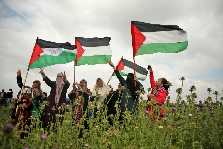 Image: Palestinian women wave Palestinian flags and flash the victory gesture during a protest near the border with Israel east of Jabalia in the Gaza strip, commemorating Land Day on March 30, 2018.