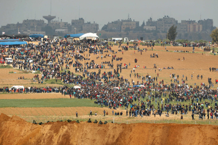 Image: Palestinians participate in a tent city protest commemorating Land Day, with Israeli soldiers seen below in the foreground, March 30, 2018.