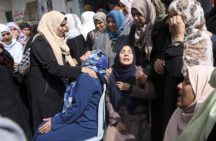 Image: Relatives mourn as the crowd carries the body of Hamdan Abu Amsha, 23, during his funeral in front of his family house in Beit Hanoun, Gaza Strip, on March 31, 2018.