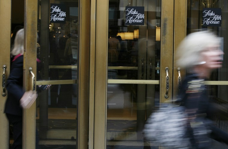 Image: People walk by the Saks Fifth Avenue store in New York