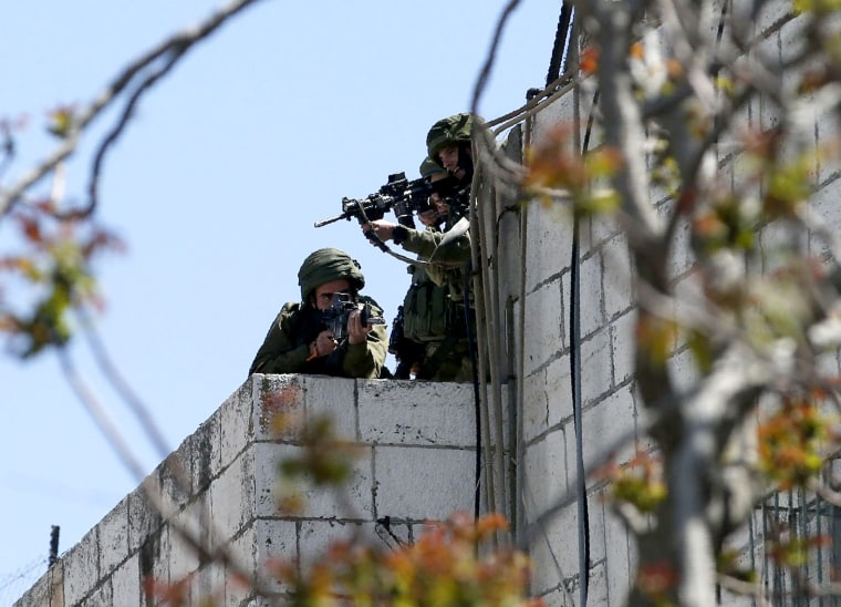 Israeli forces aim their weapons towards Palestinian demonstrators in the occupied West Bank city of Hebron on March 31.