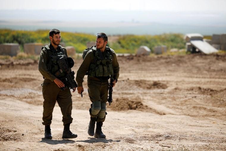 Israeli soldiers walk on the Israeli side of the border on April 1.