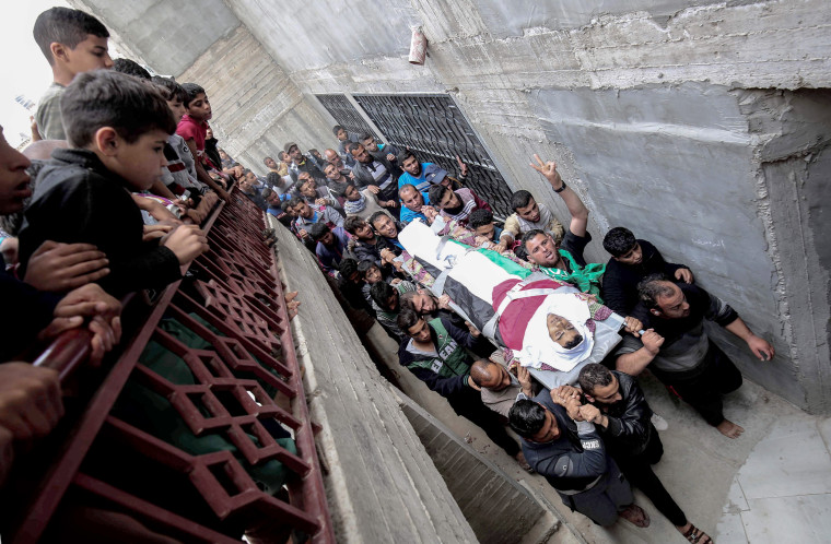 Palestinian mourners carry the body of Ibrahim Abu Shaer, who was killed on March 30 by Israeli forces, during his funeral in Rafah, in the southern Gaza Strip, on March 31.