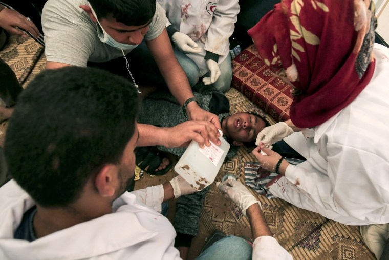 Medical staff help an injured Palestinian man at an emergency medical tent near the border with Israel, east of Khan Yunis, in the southern Gaza Strip, on April 1.
