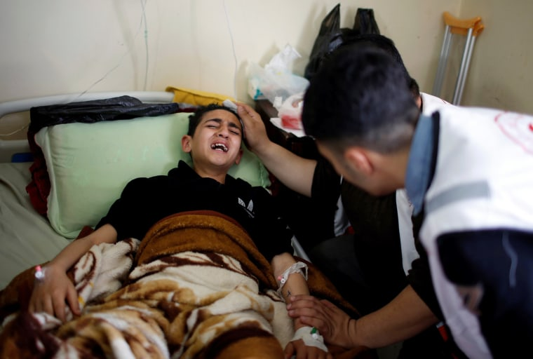 A young Palestinian boy who was wounded in the clashes is surrounded by family at al-Shifa hospital in Gaza City on April 1.