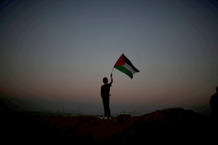 A boy waves a Palestinian flag at the Israel-Gaza border, during clashes with Israeli troops, at a tent city protest commemorating Land Day, to demand the right to return to their homeland, east of Gaza City on April 1, 2018. Land Day marks the killing of six Arab Israelis during 1976 demonstrations against Israeli confiscations of Arab land.
