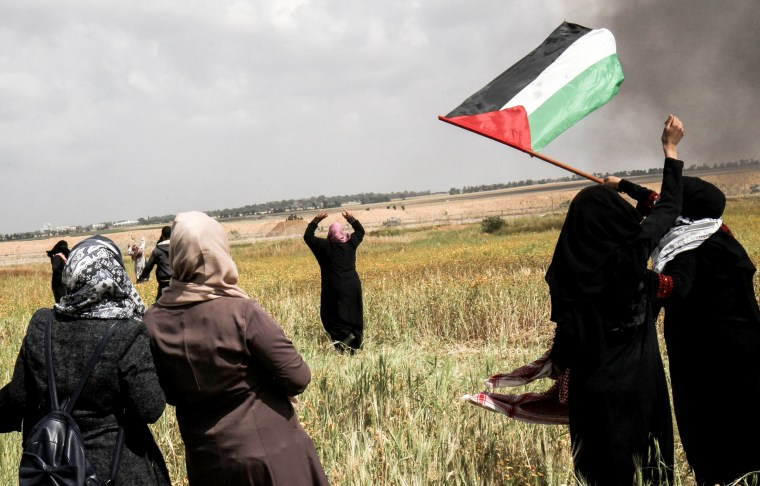 Palestinian women wave their national flag and gesture near the border, east of Khan Yunis, on March 30.