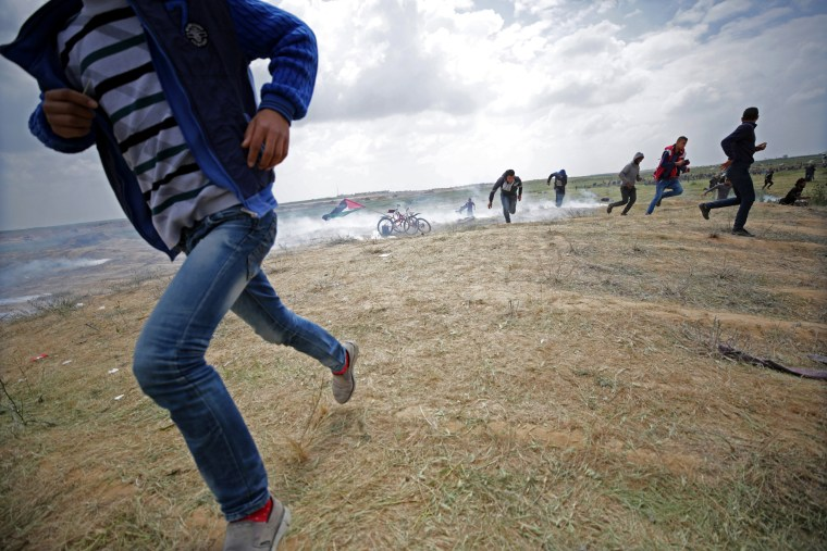 Palestinian protesters run for cover from Israeli tear-gas on March 30.
