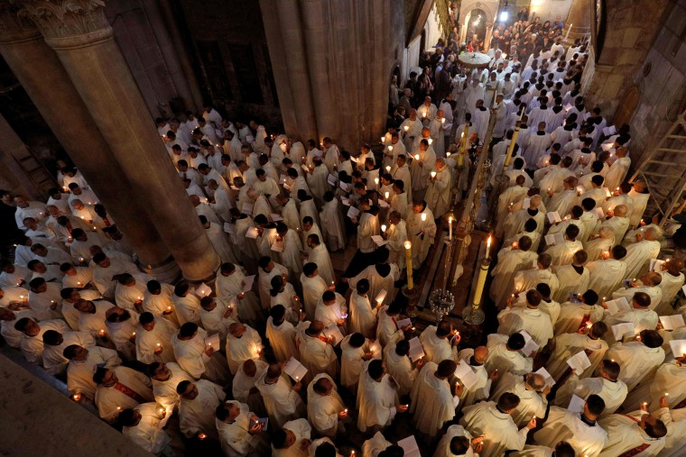 Image:  Roman Catholic clergymen hold candles as they circle the Anointing stone during Holy Thursday (