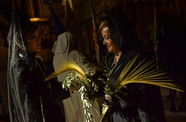 Image: Two devotees known as ''La Manolas'' take part in a Palm Sunday procession