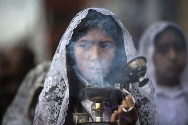 Image: A girl burns incense while taking part in a Holy Week procession in Lima