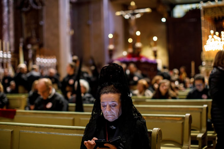 "Image: A penitent, dressed in Spanish traditional attire, checks her phone as she waits for the start of the ""Los Estudiantes"" procession during Holy Week in Madrid"