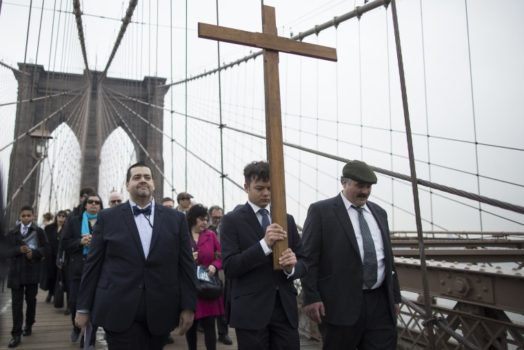 Image: Vladimir Kuzmin carries the cross during a Stations of the Cross procession on the Brooklyn bridge