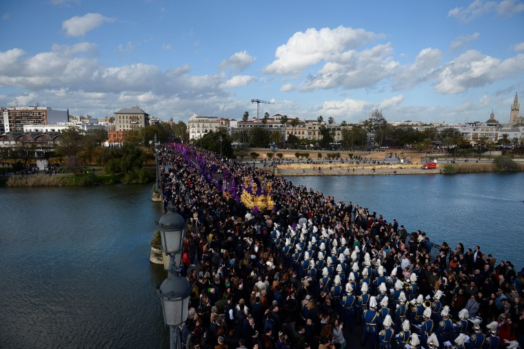 "Image: Penitents of the ""La O"" brotherhood parade over Triana bridge during a Good Friday procession"