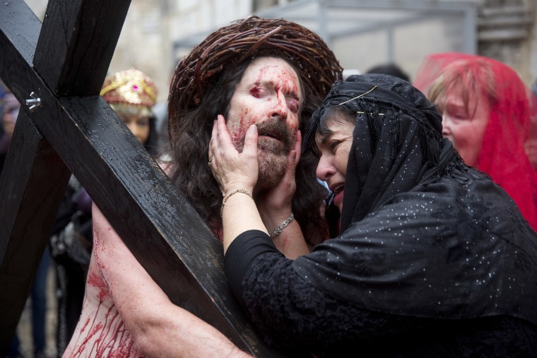 Image: An actor dressed as Jesus Christ carries a cross as he reenacts the crucifixion walk along the Via Dolorosa