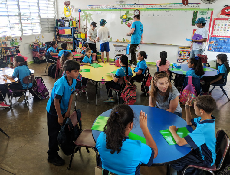Image: Former Obama adminstration officials visit students at the Isaac del Rosario Elementary School in Catano, Puerto Rico