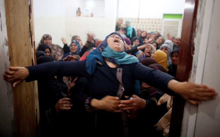 Mourners hold back a relative of Palestinian Hamdan Abu Amshah, who was killed along Israel border with Gaza, during his funeral in Beit Hanoun, in the northern Gaza Strip on March 31.