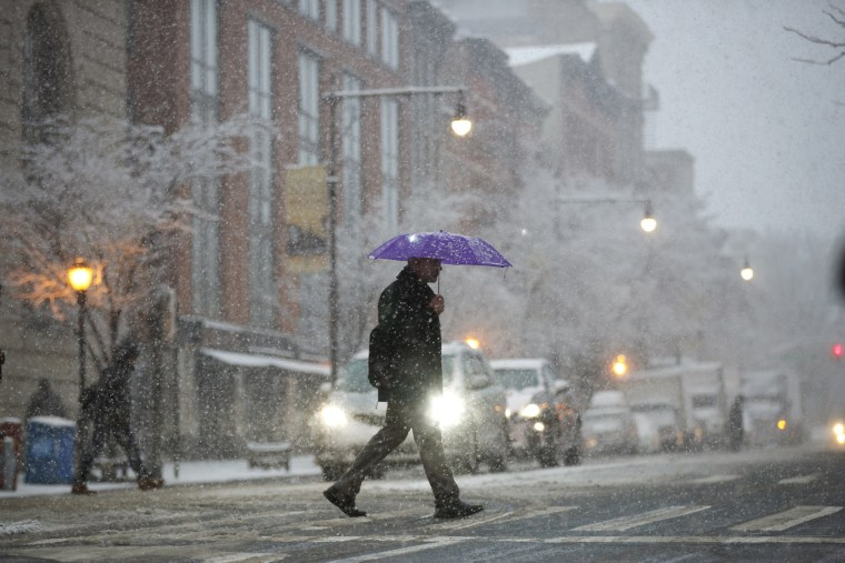 Image: Pedestrians cross the street during a snowstorm in New York