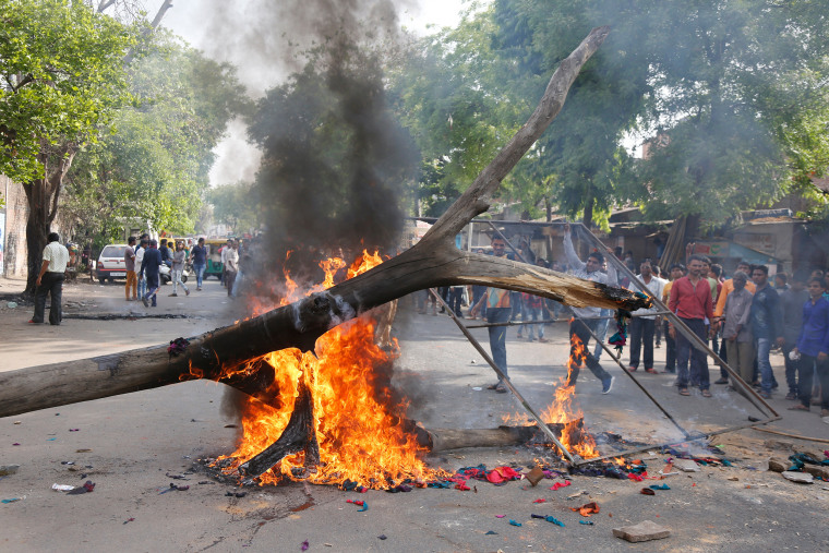 Image: Dalits burn a dead tree to block traffic during a nationwide strike