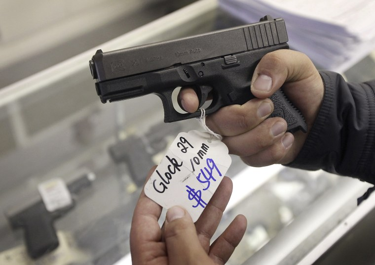 Image: A customer looks at a Glock 29 10mm hand gun at the Guns-R-Us gun shop in Phoenix