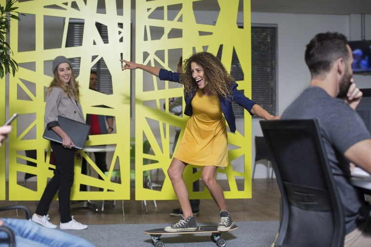 Image: Woman on skateboard in office having fun