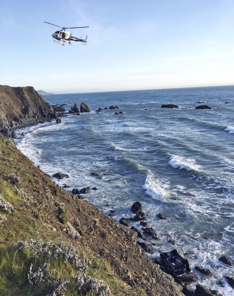 Image: A helicopter hovers over steep coastal cliffs at the scene of a car crash