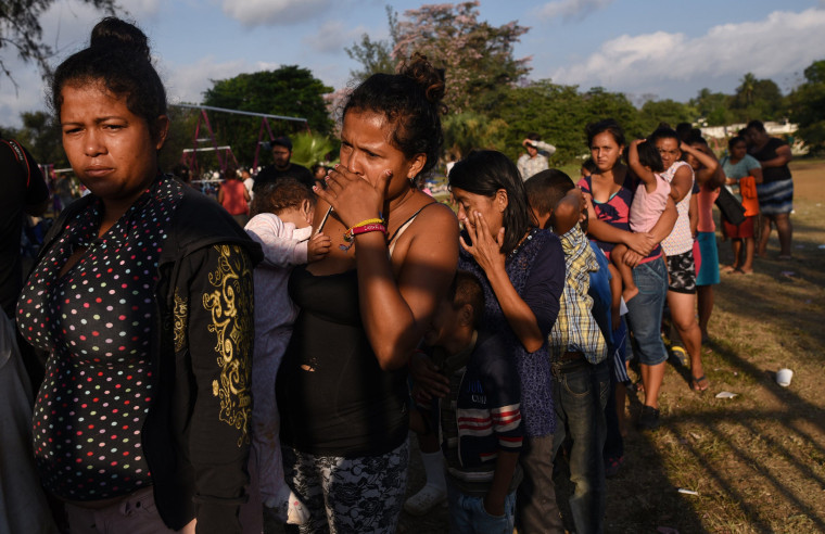 """Image: Central American migrants taking part in a caravan called \""""Migrant Via Crucis\"""" stand in line for food at a sports field"""