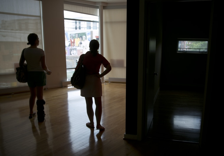 Image: Potential homebuyers look at a condominium for sale in Washington