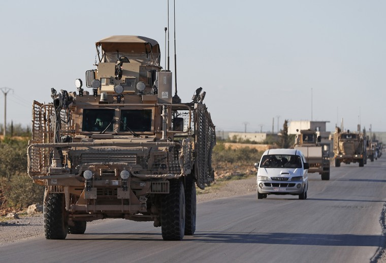 A convoy of U.S. troops drive on a road leading to the tense front line with Turkish-backed fighters in Manbij, north Syria, on Saturday.