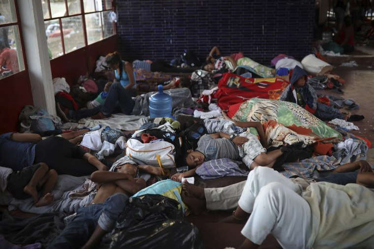 Image: Central American migrants sleep inside a sports center in Matias Romero