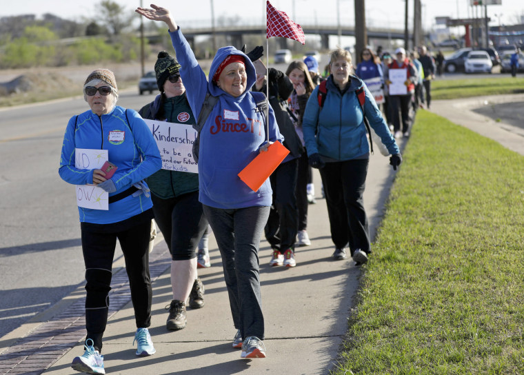 Julie Reagle, a teacher at Edison Preparatory School, waves to supporters as educators walk from Tulsa to the Oklahoma state Capitol to protest education funding on Wednesday.