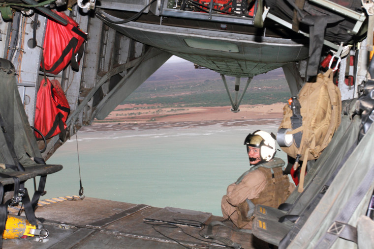 Image: A Marine assigned to Marine Medium Tiltrotor Squadron (VMM) 166, mans the rear cargo hatch during a flight over Camp Lemonnier and surrounding area