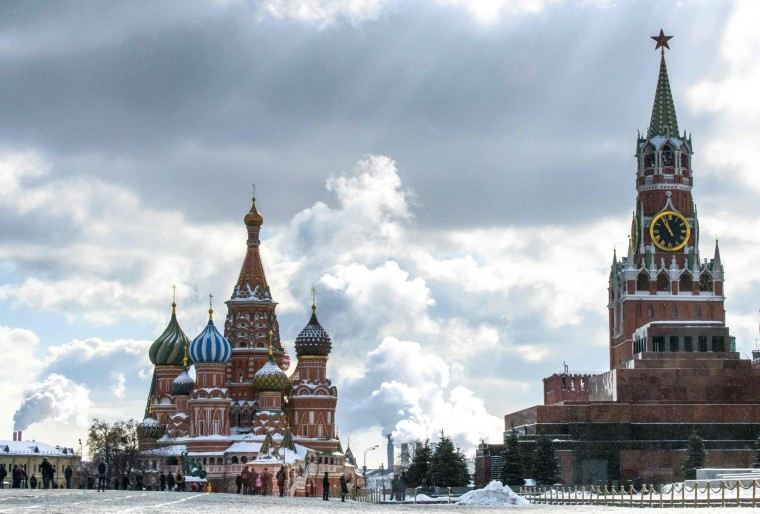 Image: People walk in front of St. Basil's Cathedral and the Kremlin on Red Square