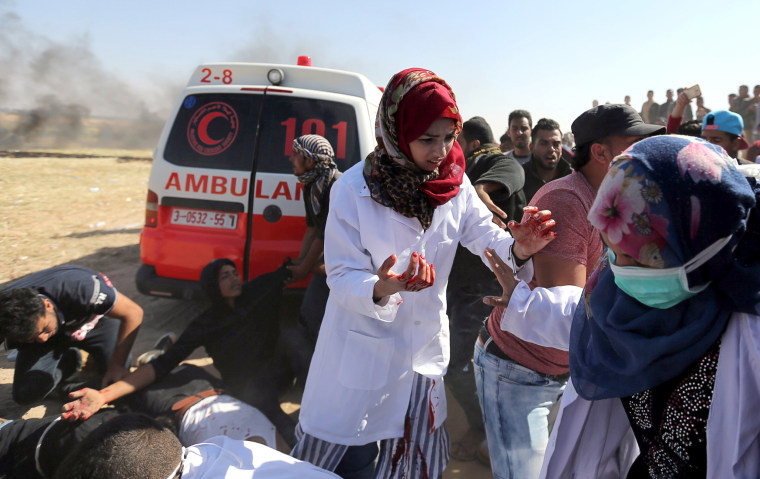 Female Palestinian medic Razan Al-Najar treats injured protesters who were wounded in clashes at the Israel-Gaza border, in the southern Gaza Strip on April 1.