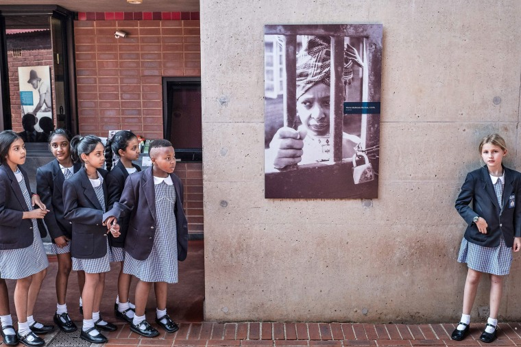 South African schoolchildren pause next to a portrait of the late South African, anti-apartheid campaigner Winnie Madikizela-Mandela, wife of African National Congress (ANC) leader Nelson Mandela, at her house in Soweto on April 4.