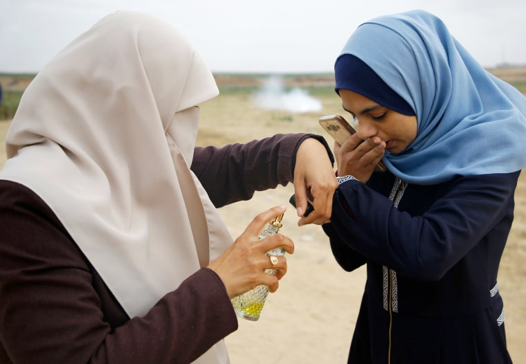 A Palestinian woman sprays perfume on the hand of her daughter to cover the smell of tear gas fired by Israeli forces during clashes along the border with Israel on April 3.